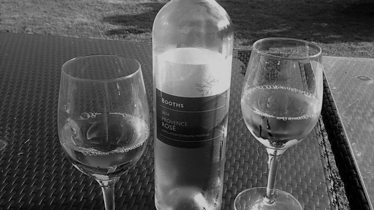 A bottle of white with two half full wine glasses on a table in the garden representing tax reductions