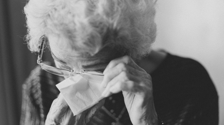 Old woman uses tissue to wipe away tears. She is sad because she is getting restricted tax relief.