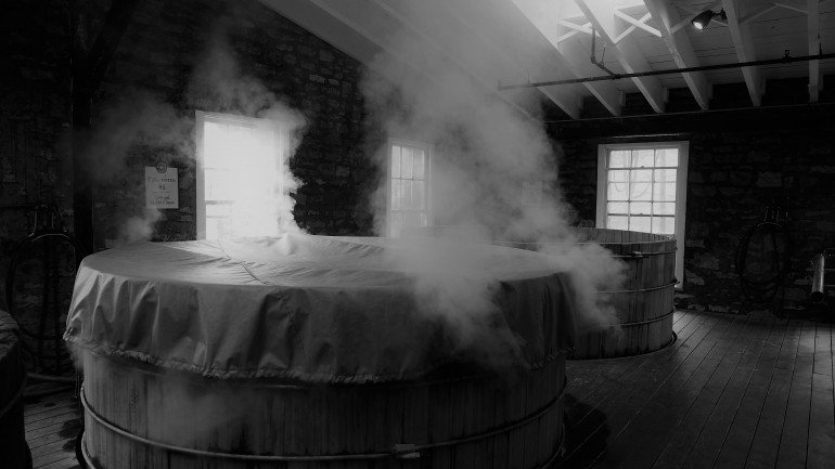 Steam rises from a covered hot tub in a small room lit by two window and a skylight representing the disappearance of VAT on tips